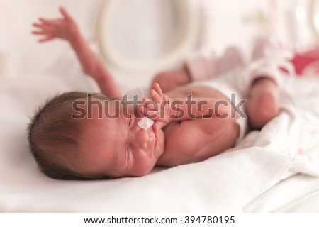 Premature newborn  baby girl in the hospital incubator after c-section in 33 week - stock photo