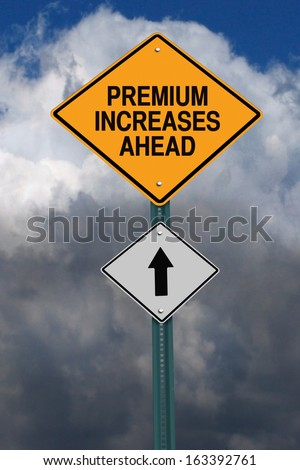 premium increases ahead road sign over dark blue sky with clouds - stock photo