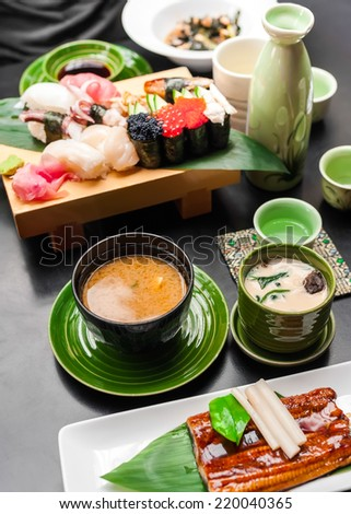 Premium quality grilled eel, miso soup, sake and sushi rolls served in Japanese restaurant. Asian food background - stock photo