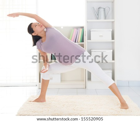 Prenatal health concept. Full length healthy 8 months pregnant calm Asian woman meditating or doing yoga exercise at home. Relaxation yoga side stretching pose. - stock photo