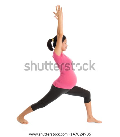 Prenatal yoga class. Full length healthy Asian pregnant woman doing yoga exercise stretching at home, full body isolated on white background. Yoga positions warrior pose 1. - stock photo