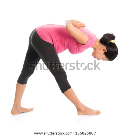 Prenatal yoga class. Full length healthy Asian pregnant woman doing yoga exercise stretching, full body isolated on white background. Yoga positions standing forward bend.