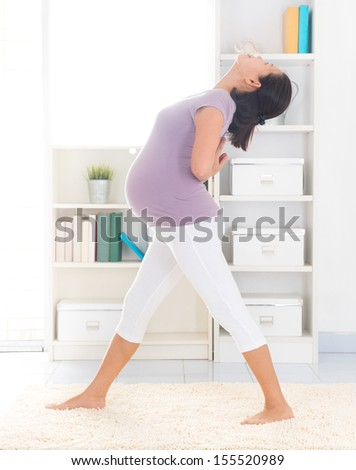 Prenatal yoga. Full length healthy 8 months pregnant calm Asian woman meditating or doing yoga exercise at home. Relaxation yoga stretching pose. - stock photo