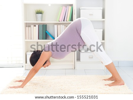 Prenatal yoga meditation. Full length healthy 8 months pregnant calm Asian woman meditating or doing yoga exercise at home. Relaxation yoga facing downward dog positions. - stock photo