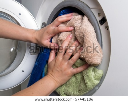 Preparation and loading clothes in the washing machine - stock photo