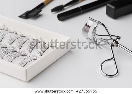 Preparation before going out starts with make-up. Nice equipment for making eyes look flawless. Curler, brushes, false eyelashes and pencil are everything needed for eyes. - stock photo