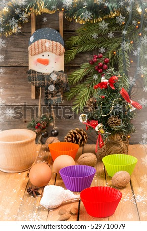 Preparation Christmas New Year sweeties. Ingredients and holiday decorations over on wooden table against old wooden background with fir tree branch, small Christmas tree and snowman.