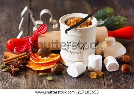 Preparation for baking Christmas cookies. Brown sugar, spices, marshmallow, nuts, rolling pin and cookie cutters on wooden kitchen table. - stock photo