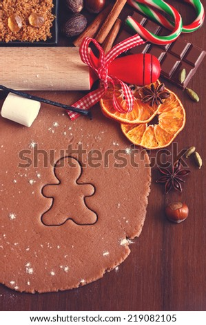 Preparation for baking Christmas cookies. Gingerbread dough with spices gingerbread man cookie and rolling pin. Toned photo. - stock photo