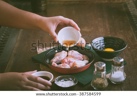 Preparation for cooking in home kitchen. woman left hand pouring soil sauce into fry pan to mix with chicken wings - stock photo