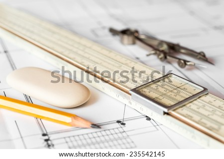 Preparation for drafting papers, the tools and schemes on the table. Angle view, focus on a compass - stock photo