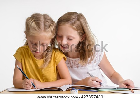 Preparation for examination is very important for children. Two lovely sisters help each other to do their homework. The elder sister is interested in evolution of the child. - stock photo
