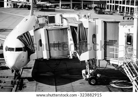 Preparation for fly with white airplane and jet bridge at the airport on black and white color - stock photo