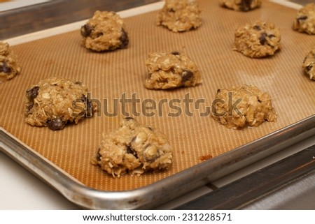 Preparation for fresh homemade chocolate chip oatmeal cookie dough baker. These are snack prepared baked on sheet of pans.  - stock photo