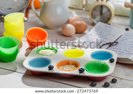 Preparation for sweet cupcakes with blueberries - stock photo