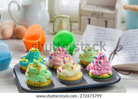 Preparation for sweet muffins with cream and decoration - stock photo