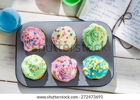 Preparation for tasty cupcakes with cream and decoration - stock photo