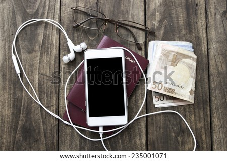 Preparation for travel, cell phone, money, passport  on wooden table - stock photo