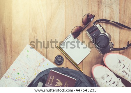 Preparation for travel,trip vacation, tourism mock up of road map,compass,camera,shoes,sunglasses ,notebook,passport Backpack ,on wooden table.