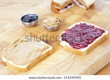 Preparation of a peanut butter and kelly sandwich - stock photo