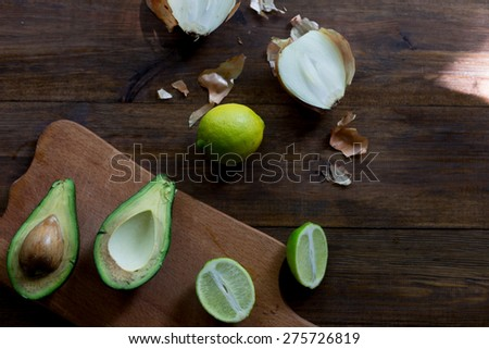 preparation of avocado guacamole in process all ingredients on table lime, onion, avocado all organic and fresh on dark wood rustic style background soft focus overhead-angle shot - stock photo