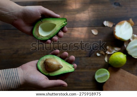 preparation of avocado guacamole in process all ingredients on table lime, onion, avocado all organic and fresh on dark wood rustic style background with male hands holding avocado overhead-angle shot
