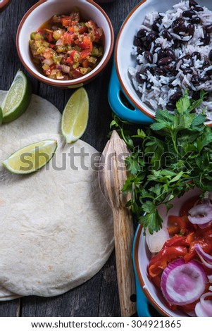Preparation of classic street food burritos on rustic table - stock photo