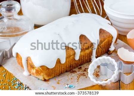 Preparation of Easter cake with icing sugar. Traditional Easter baking, products and ingredients on a wooden table. Selective focus - stock photo