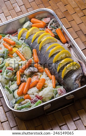 preparation of frozen fish and vegetables for the baking - stock photo