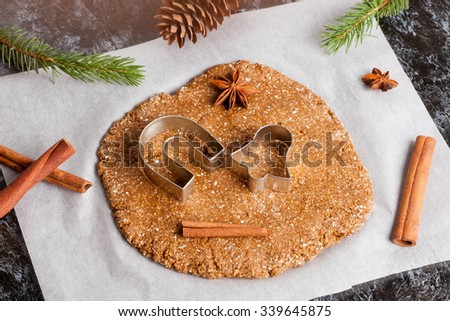 Preparation of gingerbread cookies. Cookie dough, cookie cutters on parchment paper surrounded with christmas tree branch, spices and pine cones, close up, top view, horizontal - stock photo