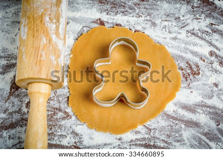 Preparation of gingerbread man cookies. Cookie dough, cookie cutter on parchment paper - stock photo