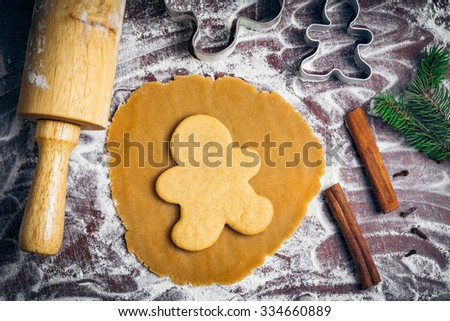 Preparation of gingerbread man cookies. Cookie dough, cookie cutters and ready baked cookies on parchment paper surrounded with christmas tree branch, spices and rolling pin - stock photo