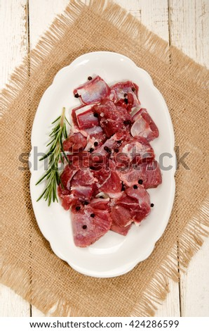 preparation of raw deer goulash with rosemary, peppercorn on an oval kitchen plate - stock photo
