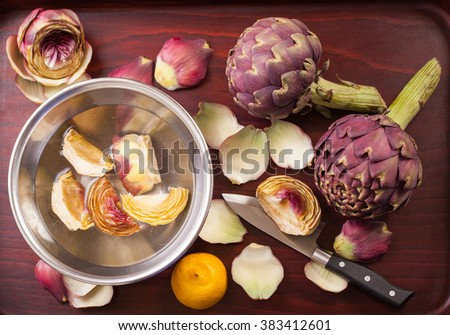 Preparation of raw purple artichokes in water with lemon juice on a wooden tray, horizontal  - stock photo