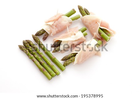 Preparation of rolls of meat, cheese and green asparagus - stock photo