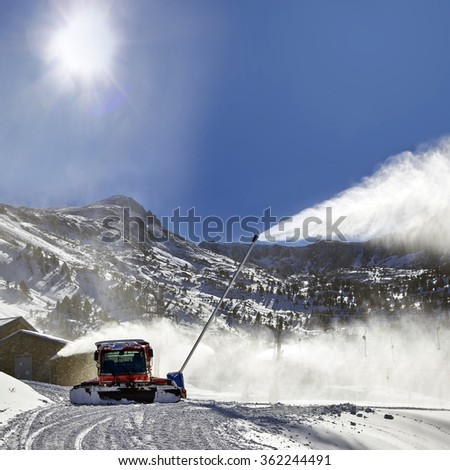 Preparation of ski resort in Pyrenees by red ratrack vehicle and snow canon