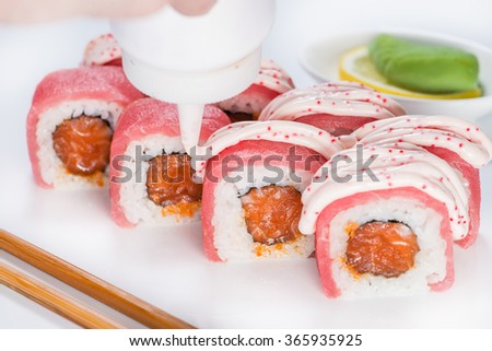 preparation of sushi, the process of pouring the sauce on the salmon roll (shallow DOF) - stock photo