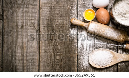 Preparation of the dough. Ingredients for the dough - Eggs and flour with a rolling pin. On wooden background. Free space for text . Top view - stock photo