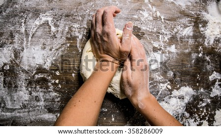Preparation of the dough. Preparation of the dough the women's hands. On a wooden table.  Top view - stock photo