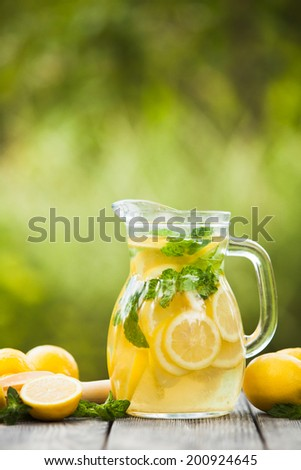 Preparation of the lemonade drink. Lemonade in the jug and lemons with mint on the table outdoor - stock photo
