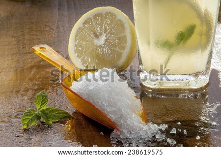 Preparation of the lemonade drink with mint and a scoop of lemon on the table - stock photo