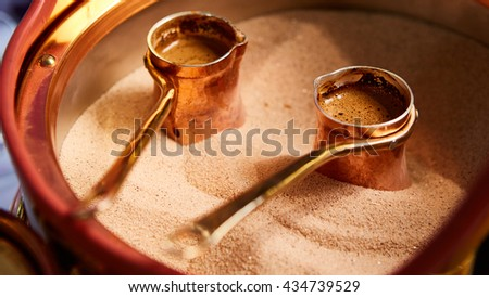 Preparation of Turkish coffee in the cezve in the sand at cafe bar