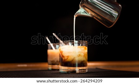 Preparation of white russian cocktails on the bar counter on rubber mat. Shallow DOF and marsala tonned - stock photo