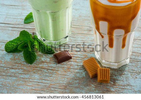 Preparation process of milkshakes with kiwi, vanilla and caramel. Tasty drink with the sweet combination of ice cream and milk with the other ingredients as toffee and leaves of mint. - stock photo