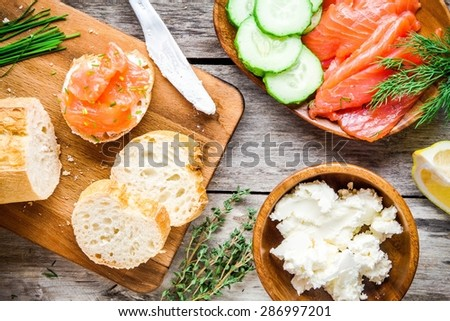 preparation sandwiches with smoked salmon: baguette with cream cheese, dill and cucumber - stock photo
