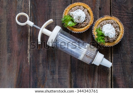 Preparation tartlets with liver paste, ricotta and lettuce using culinary syringe - stock photo