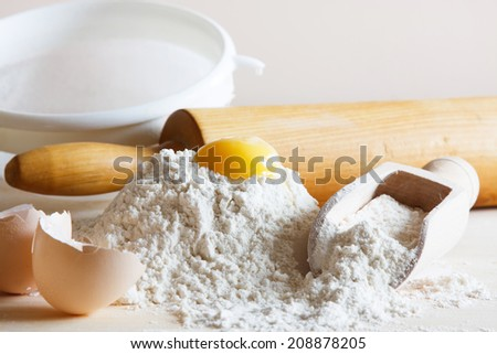 Preparations for homemade baking. Flour and egg on table - stock photo