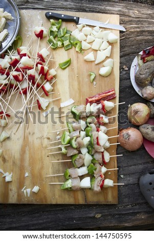 Preparatives for vegetable brochettes camping over a wooden table. - stock photo