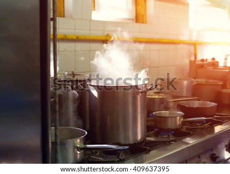 Prepare a lot of food. In a saucepan, boil the water. Cook. Restaurant kitchen. The restaurant's cuisine. Hot time. Industrial kitchen. Cooking food - process. - stock photo