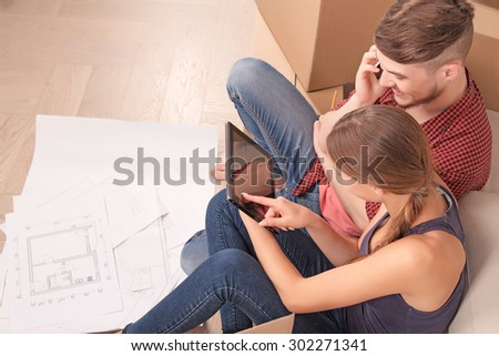 Prepare for living. Pleasant young wife sitting near settee and holding laptop while pointing it to her husband talking on mobile phone. - stock photo